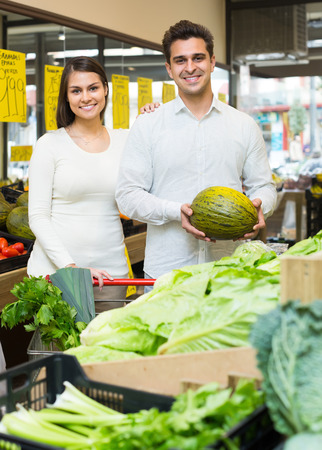eating fruits: Portrait of cheerful young couple choosing fruits and vegetables, prices on Spanish
