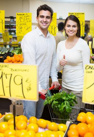 armenian woman: smiling russian family couple buying fresh seasonal fruits in market