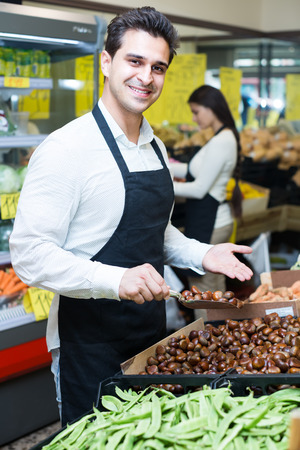sellers: Happy sellers with chestnuts in market Stock Photo