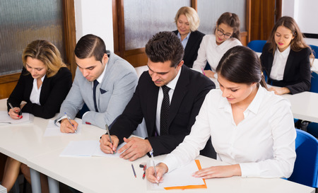 attentive: Group of attentive adult students at the desks at business training