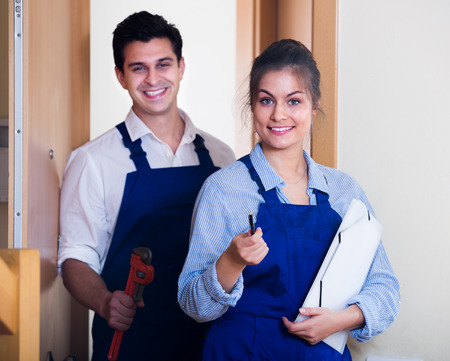 tooling: Happy handyman and female assistant in uniform with tooling in hall Stock Photo
