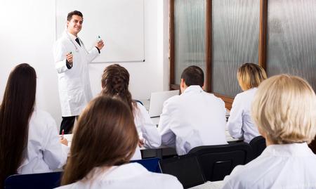 profesor: pasantes multinacionales jóvenes y feliz Profesor que tiene discusión en Facultad de Medicina Foto de archivo