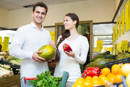 spouses: Happy young spouses choosing veggies in grocery store together