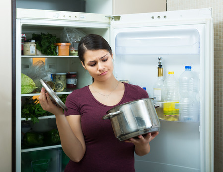loathsome: Amazed brunette female sniffing at foul food from casserole