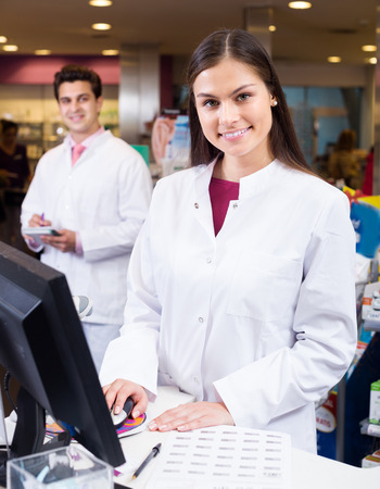 armenian woman: Cheerful pharmacist standing at pay desk and pharmacy technician helping indoors