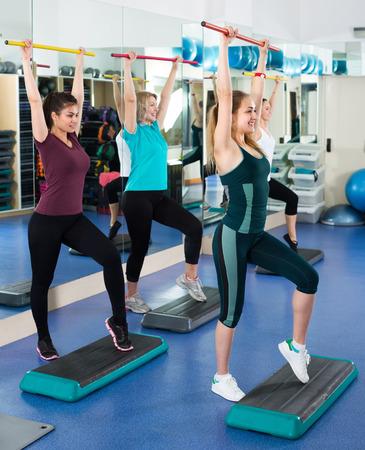 gimnasia aerobica: diferentes mujeres en edad felices que tienen tren aer�bico grupo en plataformas de paso en el club de deporte. enfoque selectivo