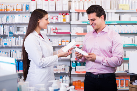 farmacy: Woman pharmacist counseling customer about drugs usage in modern farmacy