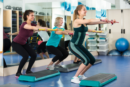 gimnasia aerobica: Grupo de mujeres de edad diferentes alegres que el tren aer�bico en el gimnasio. enfoque selectivo Foto de archivo