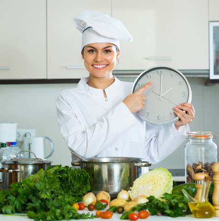 checking ingredients: Smiling young woman in uniform cooking vegetables and looking at clock Stock Photo