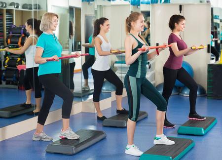 aerobics: Las hembras que se resuelven en la plataforma de paso aer�bico en el gimnasio moderno