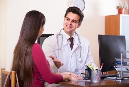 患者と近代的なクリニックでデスクで治療学者の肖像画 写真素材