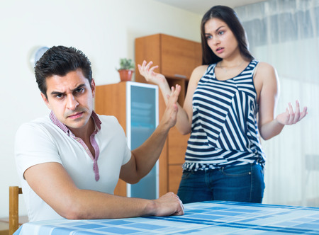 enmity: Sulking young man and longhaired girl blaming each other during home quarrel