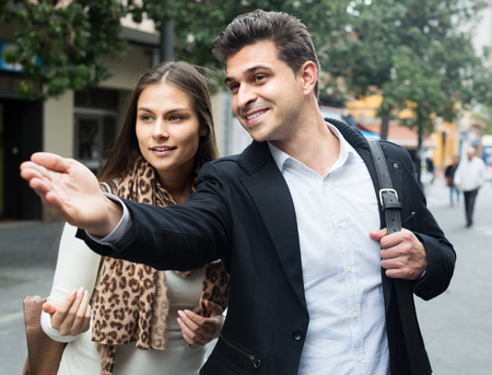 sidewalk talk: Lost woman asking handsome happy stranger to show direction outdoor Stock Photo