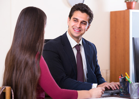 conduction: Smiling insurance agent serving and consulting confused customer indoors Stock Photo