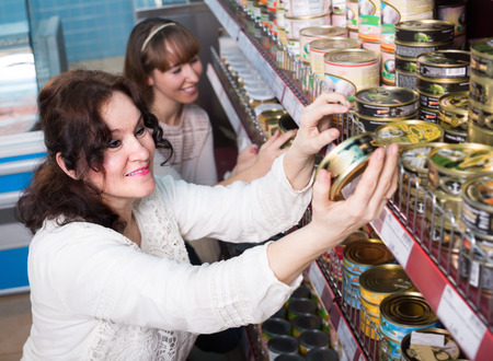 canned goods: Smiling mature and young buyers choosing canned goods in food store