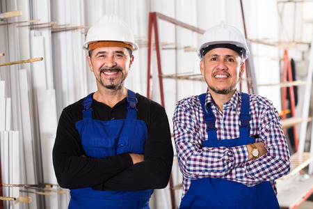 depository: Two positive specialists in helmets and workwear posing at workshop Stock Photo