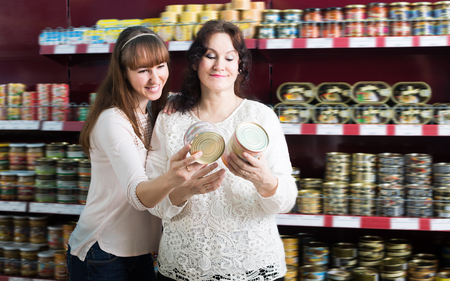 tinned: Female customers selecting tinned products at grocery Stock Photo