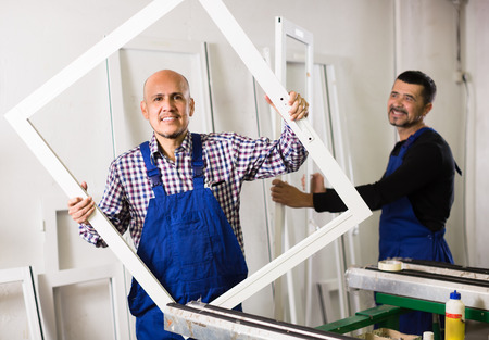 Two smiling workmen in coverall with different PVC windows and doors Stock Photo