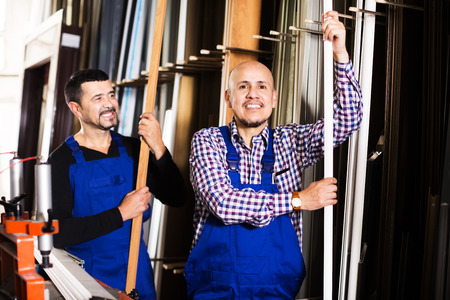 glasswear: Two smiling labours inspecting PVC manufacturing output in workshop Stock Photo