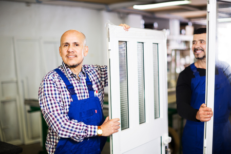 aluminium: Two smiling workers inspecting PVC manufacturing output in workshop