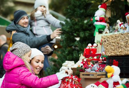 Familie von vier Kauf Weihnachtsdekorationen auf Markt. Konzentrieren Sie sich auf Frau und Mädchen Standard-Bild - 54869931