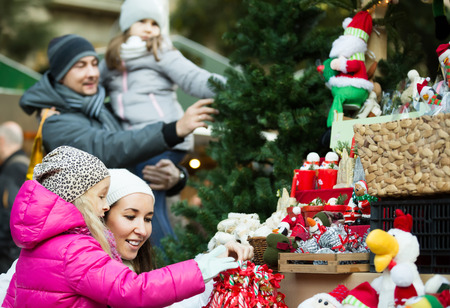 christmas market: Family of four buying christmas decorations at market. Focus on woman and girl Stock Photo