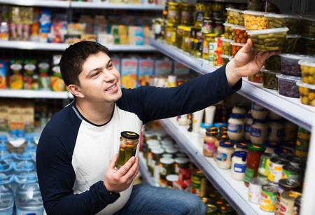 middle class: joven de clase media ordinaria choosing comida enlatada en el supermercado Foto de archivo