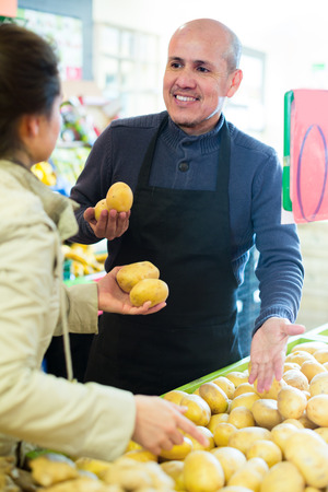 salesman: Smiling salesman serving female customer purchasing potatoes in hypermarket