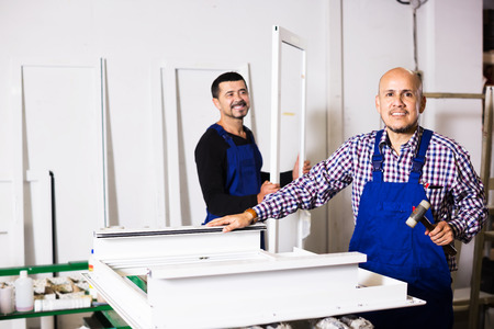 thermoplastic: Two male labours in uniform working in PVC shop and smiling