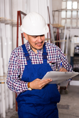 rigger: Middle age person in helmet with documents at workshop Stock Photo