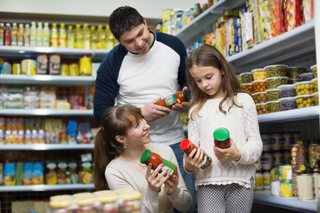 tinned: Young positive smiling parents with little girl buying tinned food at grocery