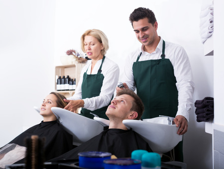 18's: Portrait of pleased customers and positive hairstylers washing hair in salon. Focus on the right guy
