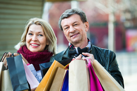 spouses: Cheerful smiling mature spouses with shopping bags in spring day