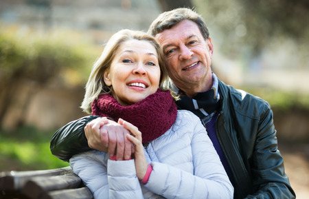 Portrait of smiling pensioners couple cuddling in park at spring day
