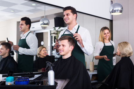 cutting hair: Positive male hairdresser cutting hair of teenage guy in barbershop Stock Photo
