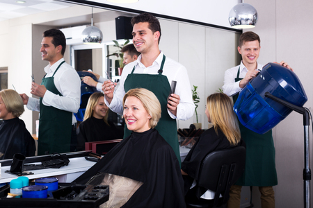 peignoir: Smiling professional stylist cutting hair of elderly blonde in salon Stock Photo