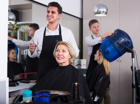18's: Dark-haired man doing hairstyle for smiling elderly blonde in hairdressing saloon Stock Photo