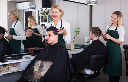 16s: Positive elderly blonde woman cutting hair of brunet guy in barbershop Stock Photo