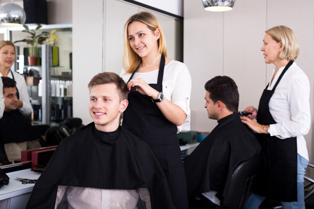 18's: Young blonde hairdresser serving teenager in salon chair. Focus on the man
