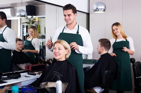18's: Smiling male stylist cutting hair of elderly blonde in salon