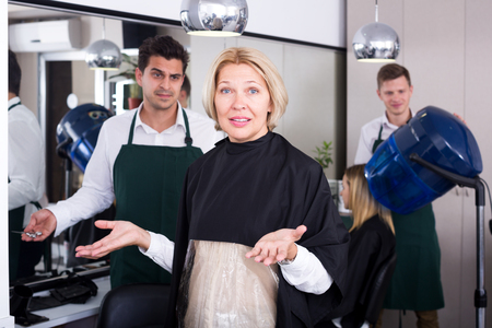 peignoir: Unhappy female pensioner having fight with hairdresser in salon. Focus on the woman Stock Photo