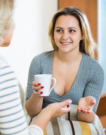 talkative: Senior woman and young girl talking and drinking tea Stock Photo