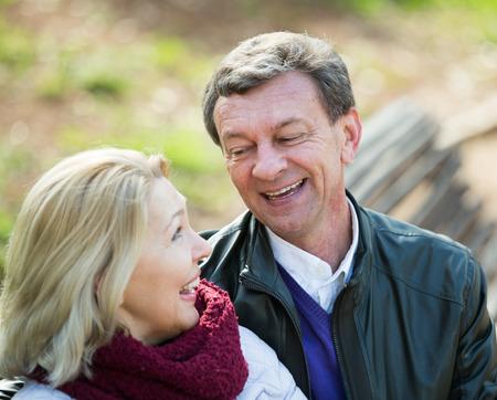amigos abrazandose: Smiling mature couple having flirting conversation in park