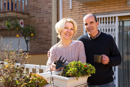 2 50: Pensioners couple on a terrace with gardening accessories and a cup of coffee