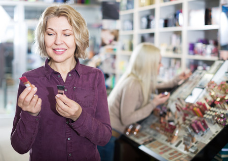 ordinary woman: Portrait of ordinary woman doing shopping in beauty store Stock Photo
