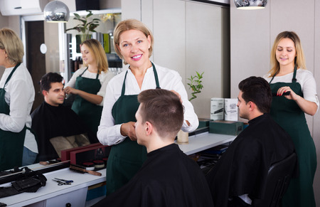 16s: Positive elderly woman hairdresser serving teenager guy in chair Stock Photo