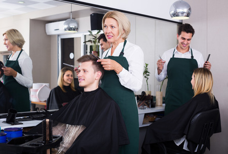 19's: Positive senior woman hairdresser serving teenager in chair