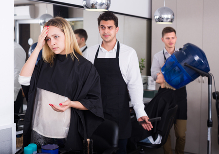 complaining: Young girl complaining on new haircut in hair salon