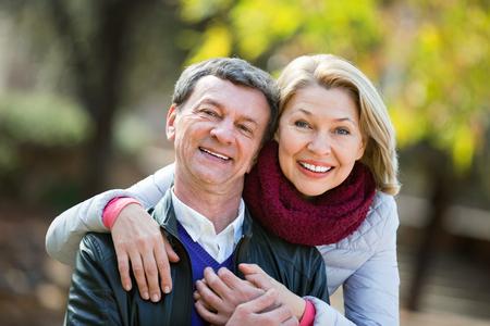amigos abrazandose: Portrait of happy charming  elderly couple in sunny spring day Foto de archivo