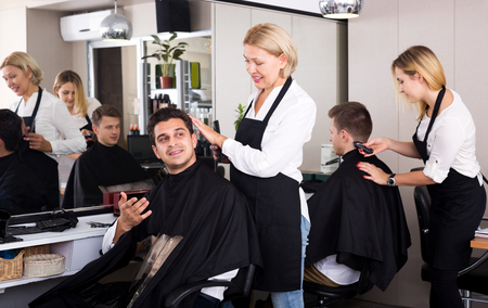 16s: Cheerful mature female doing hairstyle for adult man in hairdressing saloon
